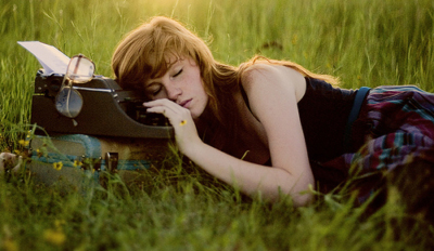 Girl in grass with typewriter